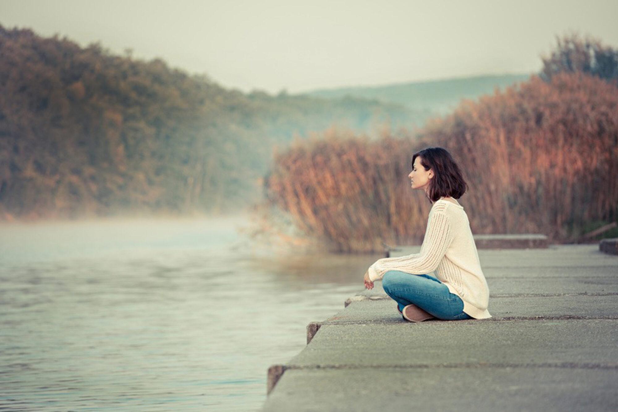 Frau sitzt auf einem Holzssteg am See