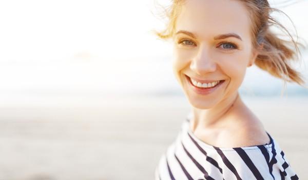 junge Frau am Strand lächelt in die Kamera