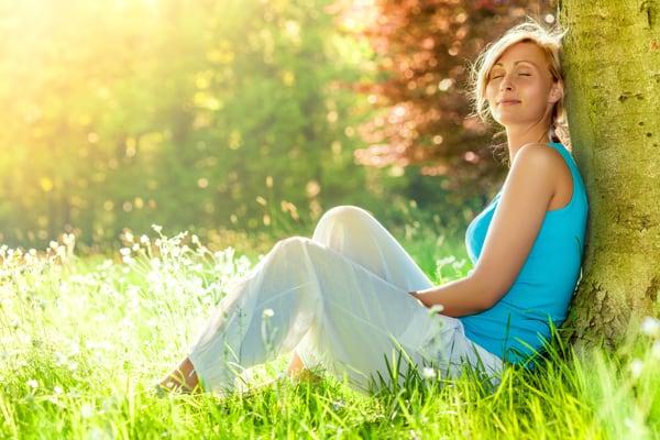 Junge Frau mit geschlossenen Augen sitz im Gras und an einen Baum gelehnt